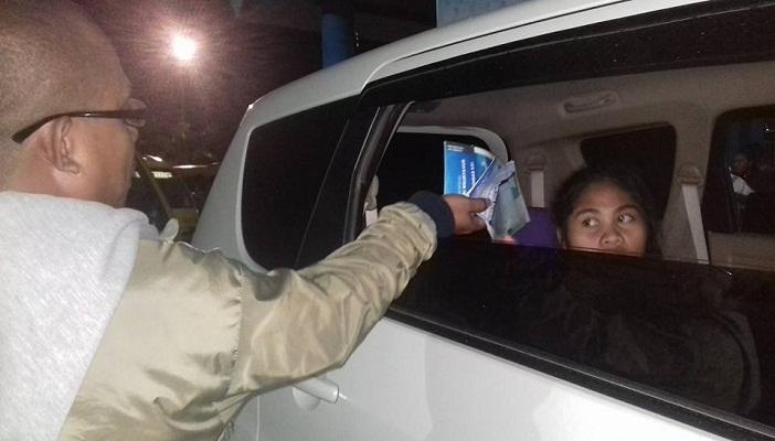 Dari balik kaca jendela mobil seorang wanita tampak heran melihat aksi bagi-bagi brosur pariwisata Kei Kecil